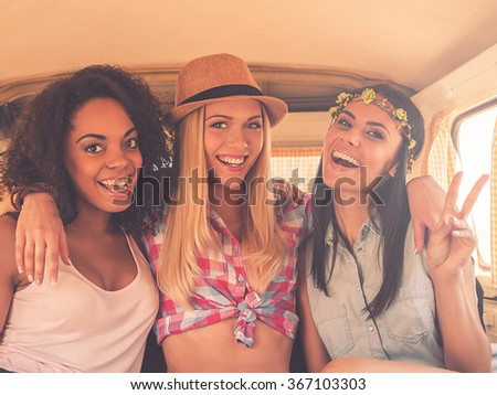 Friends forever! Three excited young women smiling at camera and gesturing while sitting inside of retro minivan - stock photo