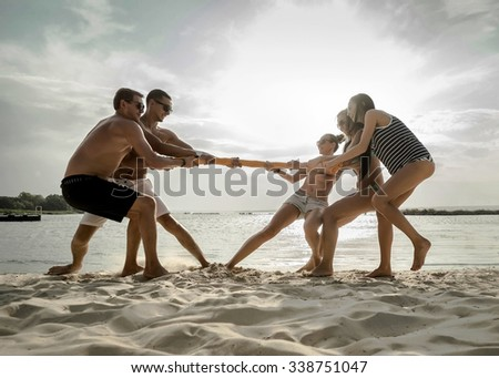 Friends funny tug of war on the beach under sunset sunlight. - stock photo
