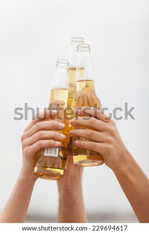 Friends gathering together to cheers at beach sunset. closeup on woman and man hands only with bottles - stock photo