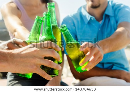 Friends gathering together to cheers at the beach sunset, hands only - stock photo