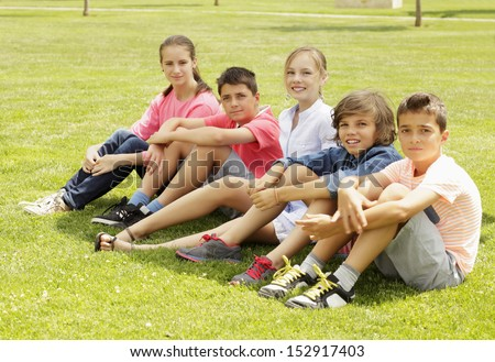 Friends. Group of children sitting in the grass in the park. - stock photo
