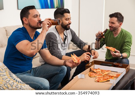 Friends hanging out at home while enjoying a slice of pizza and drinking some beer - stock photo
