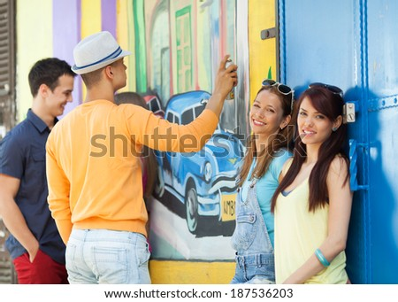 Friends hanging out by a wall in the city street - stock photo