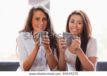 Friends having a cup of coffee while smiling at the camera - stock photo