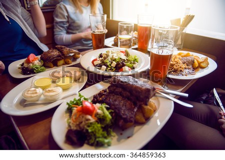 Friends having a dinner in the restaurant with salad, barbeque and beer - stock photo