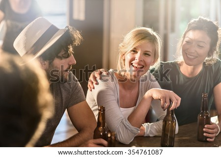 Friends having a drinks on a sunny evening in a cozy house. They are sitting at a wooden table with beers. They are wearing casual clothes. Focus on a gorgeous blonde girl touching her bottle. - stock photo