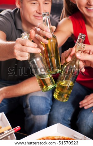 Friends having a nice little party with beer an pizza, they clink their glasses and have lots of fun - stock photo