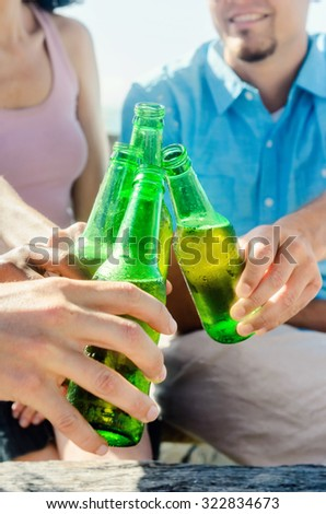 Friends having a toast with their beer drinks at a relax leisure day at the beach, sunny afternoon, hands only  - stock photo
