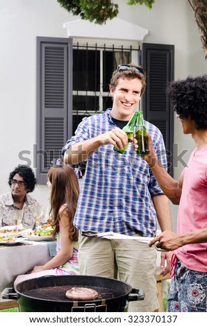 Friends having beers around a barbecue bbq at a outdoor garden party, with meat on the grill  - stock photo