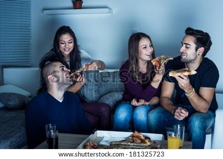 Friends having fun and eating pizza at night. Selective focus - stock photo