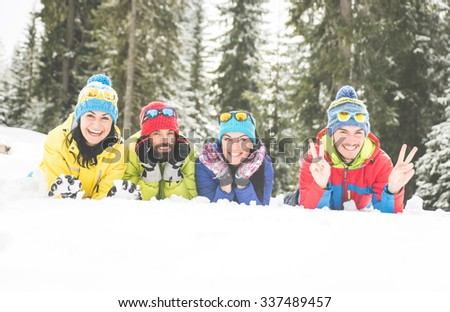 Friends having fun on the snow. lying down and enjoying the free time - stock photo