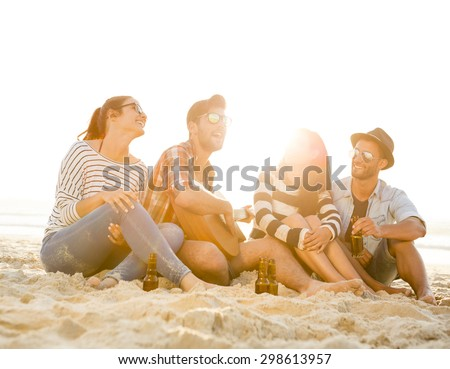 Friends having fun together at the beach, playing guitar and drinking beer - stock photo