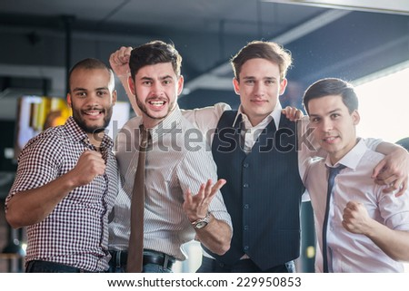 Friends having fun together. Four friends standing arm in arm at the bar and look at the TV and shout loudly and laughing. Friends having fun spending time together - stock photo