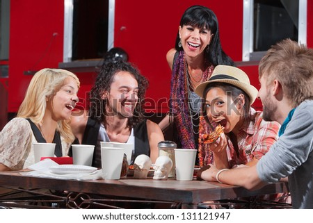 Friends having fun while eating pizza outside - stock photo