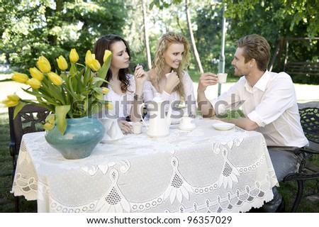 Friends having good time in summer garden - stock photo