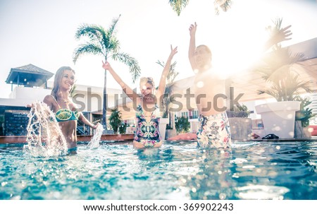Friends having party and dancing in a swimming pool - Young people enjoying vacation in a tropical resort hotel - stock photo