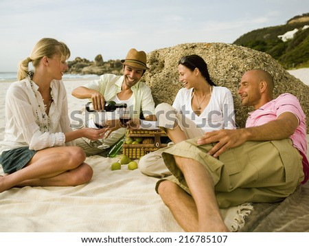 Friends having wine on the beach. - stock photo