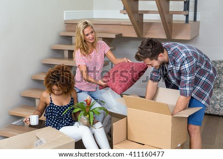 Friends helping each other while relocating at new house - stock photo