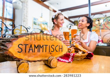 Friends in Bavarian inn toasting with beer glasses sitting at the Stammtisch - stock photo