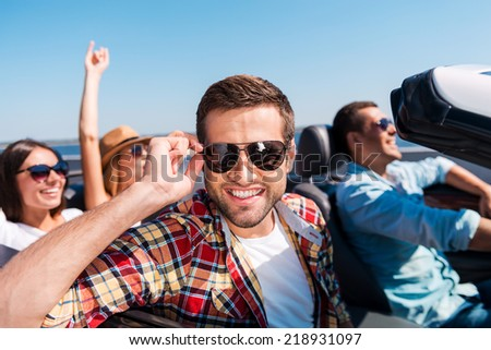 Friends in convertible. Four cheerful friends enjoying road trip in their convertible while handsome man adjusting his sunglasses and smiling - stock photo