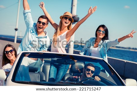Friends in convertible. Group of young happy people enjoying road trip in their white convertible and raising their arms - stock photo