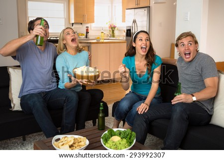 Friends in living room watching a movie on edge of their seat with popcorn - stock photo