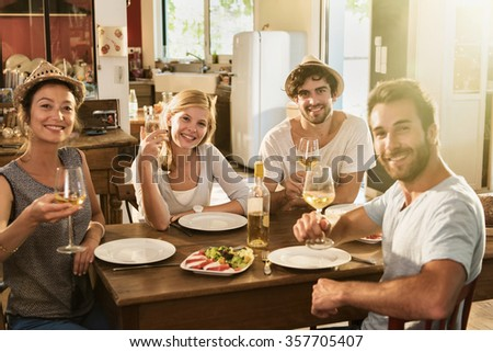 Friends in their 30's having a nice aperitif on a rustic wooden table in a lovely house. They are looking at camera and smiling in front of glasses of white wine and tomatoes mozzarella - stock photo