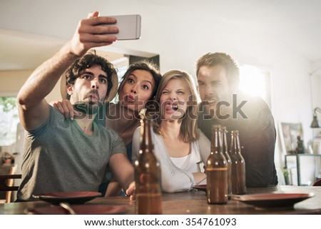 Friends in their 30's taking selfies on a smartphone in a charming house. Two men and two women are making faces while the phone is taking the picture. Backlit shot with flare, real people. - stock photo