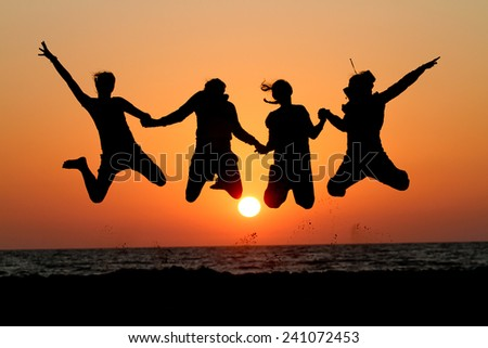 friends jumping in sunset at beach  - stock photo