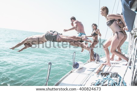 Friends jumping in the water from the boat - stock photo