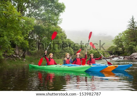 Friends kayaking together cheering at camera in a lake in countryside - stock photo