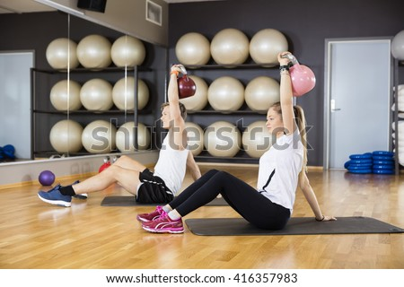 Friends Lifting Kettlebells While Sitting On Mat In Gym - stock photo