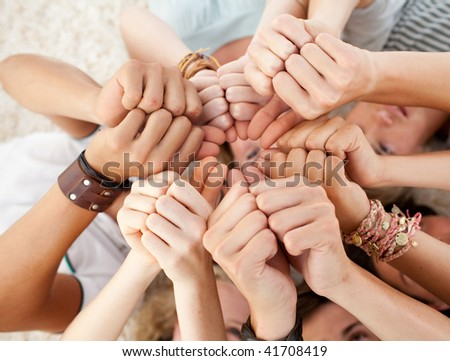 Friends lying on the floor with heads together and with thumbs up - stock photo