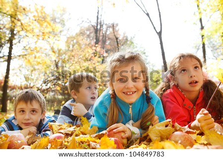 Friends lying on yellow leaves in park - stock photo