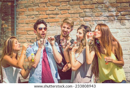 friends making soap bubbles outdoor. concept about leisure and fun with friends - stock photo