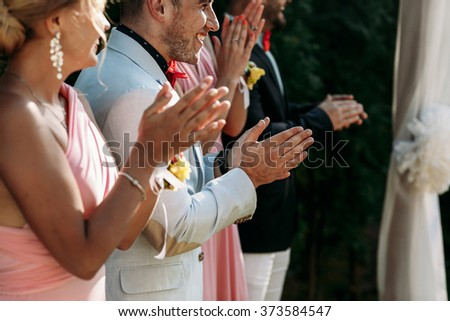 Friends of bride and groom on the wedding ceremony outdoors - stock photo