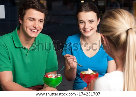 Friends of three enjoying meal at restaurant - stock photo