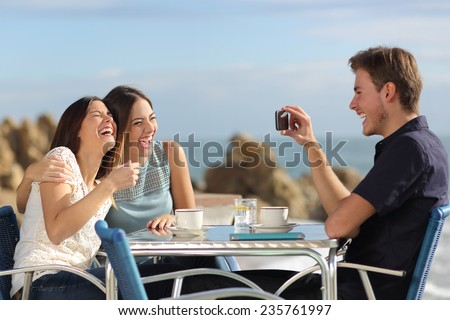 Friends on vacations laughing and taking photo with a smart phone in a restaurant on the beach - stock photo