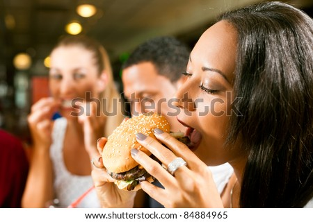 Friends - one couple is African American - eating hamburger and drinking soda in a fast food diner; focus on the woman in front - stock photo