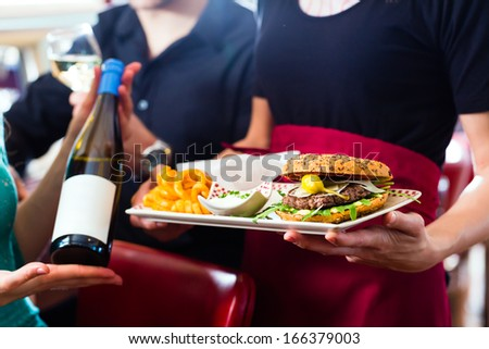 Friends or couple eating fast food in American fast food diner, the waitress serving the food and wine - stock photo