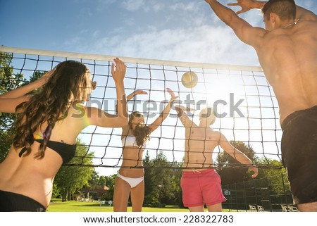 Friends play volleyball on the beach - stock photo