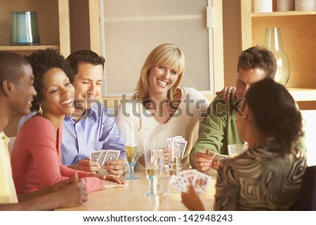Friends playing cards at table - stock photo