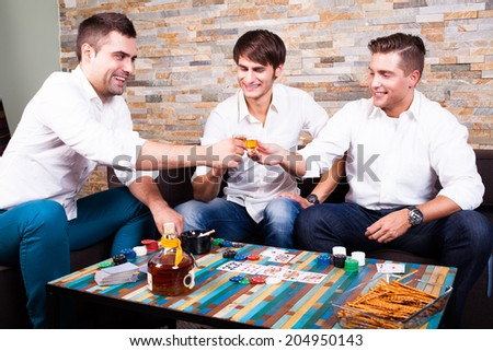 friends playing poker and drinking rum shots - stock photo