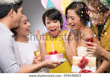 Friends presenting a birthday cake to the astonished girl - stock photo