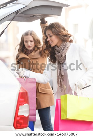 Friends putting goods into the car trunk. Two beautiful young women packing their goods into the car trunk - stock photo