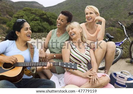 Friends singing and playing guitar - stock photo