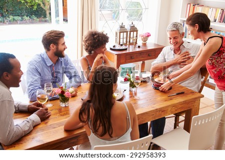 Friends sitting at a dining table celebrating a birthday - stock photo