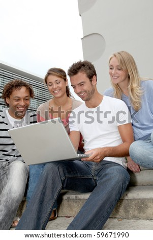 Friends sitting in stairs with laptop computer - stock photo