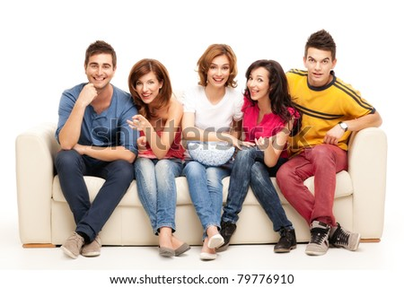 friends sitting on couch laughing at comedy movie - stock photo