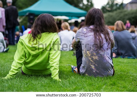 Friends sitting on the grass, enjoying an outdoors music, culture, community event, festival. - stock photo